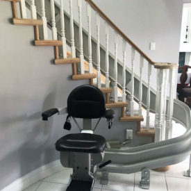 Stairlift waits for recipient at the bottom of stairs.